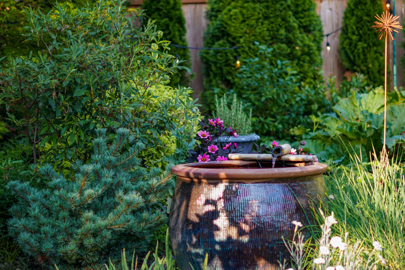 Garden Tour - water fountain made out of a planter nestled in the flowers.