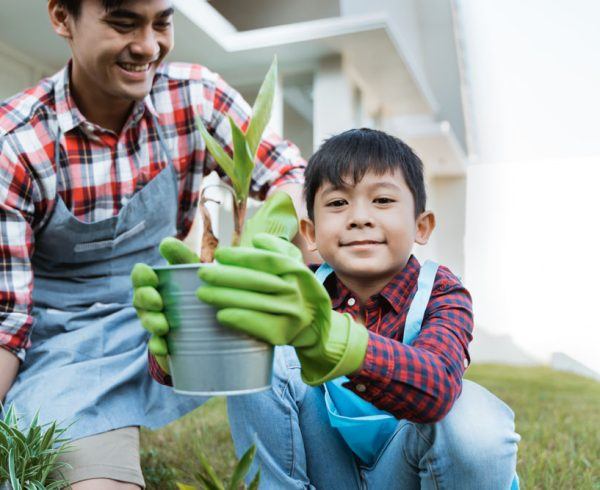 Child with gloves on holding potted plant with proud parent